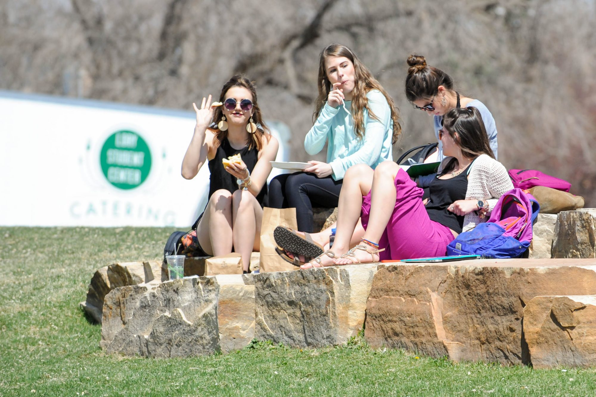 Women sitting on rocks at CSU eating food